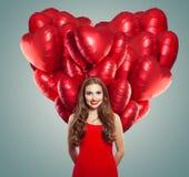Flicka i röd klänning med hjärtaballonger Härlig kvinna med röd kantmakeup, perfekt lockigt hår och gulligt leende royaltyfri fotografi