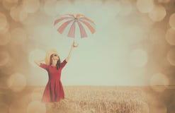 Flicka i röd klänning med paraplyet och hatten Fotografering för Bildbyråer