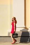 Flicka i röd klänning och med en trendig handväska royaltyfria bilder
