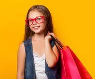 Flicka i röda exponeringsglas med shoppingpåsen Royaltyfria Bilder