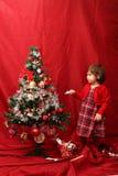 Flicka i rött och den dekorerade julgranen Arkivfoton