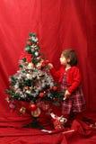 Flicka i rött och den dekorerade julgranen Royaltyfri Foto