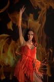 Flicka i rött på en bakgrund av brand royaltyfria bilder