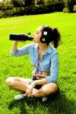 Flicka i randigt skjortasammanträde på grönt gräs Royaltyfri Fotografi