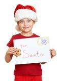 Flicka i röd hatt med bokstaven till santa - begrepp för jul för vinterferie Arkivbild