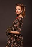 Flicka i retro stil som poserar med pälssaker. Royaltyfria Bilder