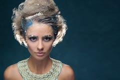 Flicka i rollen av snödrottningen på en blå bakgrund royaltyfri bild