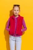 Flicka i rosa färgpälsväst Arkivbild