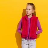 Flicka i rosa färgpälsväst Royaltyfri Bild