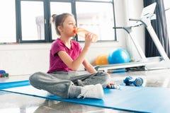 Flicka i rosa skjortasammanträde på matt yoga och dricksvatten i idrottshall Arkivfoton