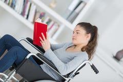 Flicka i rullstol med boken Royaltyfria Bilder