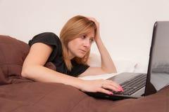 Flicka i säng med bärbara datorn Royaltyfri Fotografi