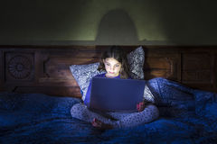 Flicka i säng med bärbara datorn, glödande ljus Arkivbild