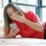 Flicka i säng med en smartphone royaltyfria bilder