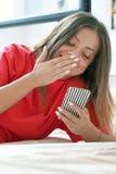 Flicka i säng med en smartphone royaltyfri fotografi