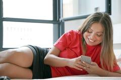 Flicka i säng med en smartphone royaltyfria foton