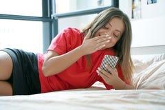 Flicka i säng med en smartphone royaltyfri foto