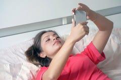 Flicka i säng med en smartphone royaltyfri bild