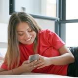 Flicka i säng med en smartphone arkivfoton