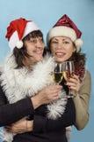 Flicka i Santa Claus hattar och champagne Royaltyfri Foto