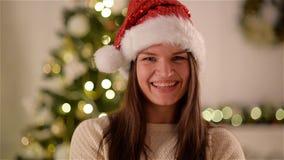 Flicka i Santa Hat med långt mörkt hår som poserar på julgranbakgrund Lycklig och emotionell kvinna som ler på lager videofilmer