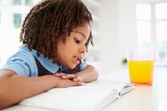 Flicka i skolalikformign som gör läxa i kök Arkivfoto
