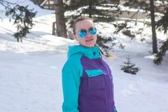 Flicka i solglasögon på en bakgrund av snö Arkivfoton