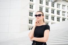 Flicka i solglasögon som poserar på trappa och bygger i Frankrike Royaltyfri Bild