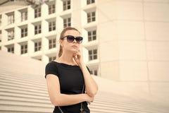 Flicka i solglasögon som poserar på trappa och bygger i Frankrike royaltyfria foton