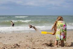 Flicka i sommarklänning som gräver på stranden royaltyfria foton