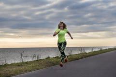 Flicka i sportdamasker och en grön t-skjorta spring längs waen arkivbilder