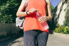Flicka i sportswear med ryggsäcken som rymmer en flaska av kallt vatten royaltyfri bild