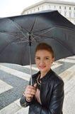 Flicka i staden som går i regnet som ler royaltyfri bild