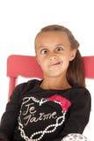 Flicka i stol som drar en rolig framsida i svart skjorta Arkivfoton