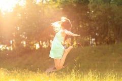 Flicka i strålarna av inställningssolen Fotografering för Bildbyråer