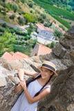 Flicka i sugrörhatt nära den forntida väggen i Eus, Frankrike fotografering för bildbyråer