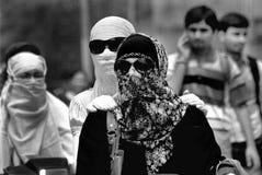 Flicka i svart, flickor som mooving med deras täckte framsida Enjoing deras frihet från damm såväl som samhälle arkivfoton