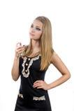 Flicka i svart klänning med doft på den vita backgrouen Fotografering för Bildbyråer