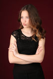 Flicka i svart klänning med korsade armar close upp mörkröd bakgrund royaltyfri bild