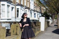 Flicka i svart klänning med prickar och solglasögon Royaltyfri Fotografi