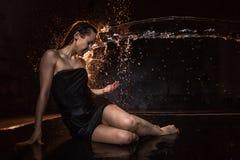 Flicka i svart klänning i vatten i en liten pöl, ström av vatten som flyger till henne, och svart bakgrund Royaltyfri Bild