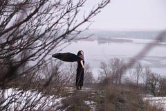 Flicka i svart klänninganseende på vägen mellan buskarna och träden Vikingkvinna med ett svärd i ett svart långt ansvar med arkivbild