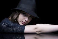 Flicka i svart med den stilfulla svart hatten Fotografering för Bildbyråer