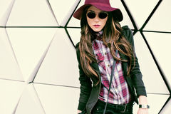 Flicka i tappninghatt och solglasögon på en stadsgata modevagel royaltyfria foton