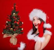 Flicka i träd för jul för santa hatt hållande. Arkivbilder