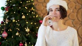 Flicka i tröja och strumpor som sitter på bakgrunden av en julgran med ett exponeringsglas av champagne firar flickan stock video