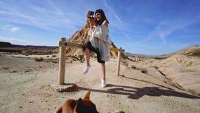Flicka i traditionell dräkt i öken med kameran