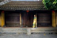 Flicka i traditionell vietnamesisk klänning i den Hoi An pagoden Royaltyfri Bild