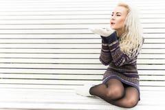 Flicka i tumvanten på att blåsa för snö slitage vit vinter för härlig stående för begreppsklänningflicka Arkivbilder