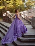 Flicka i ursnyggt purpurfärgat långt klänninganseende på trappan Royaltyfria Foton